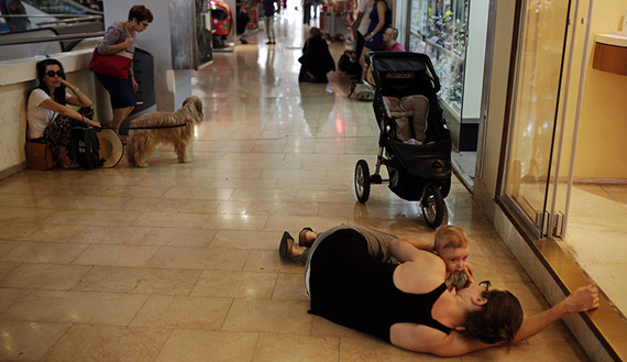 A woman lies with her baby on the floor of a shopping mall as an air-raid siren, warning of incoming rockets, sounds in Tel Aviv, July 10, 2014. (photo by REUTERS/Daniel Bar-On)