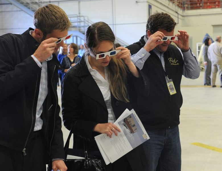 Mark Henspeter and Caitlan Dowling with the State of Alaska Department of Natural Resources and Matthew Macri, PenAir director of operations, look at a 3-D map of Wrangell-St. Elias National Park and Preserve as people gathered at the FedEx maintenance hanger at Ted Stevens International Airport to celebrate the halfway mark in the digital elevation mapping of Alaska on Tuesday, Aug. 18, 2015. Bob Hallinen / ADN