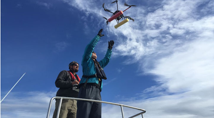 Dr. John Durban piloting the hexacopter into the hands of co-pilot Dr. Holly Fearnbach; both biologists with NOAA's Southwest Fisheries Science Center. Credit: NOAA